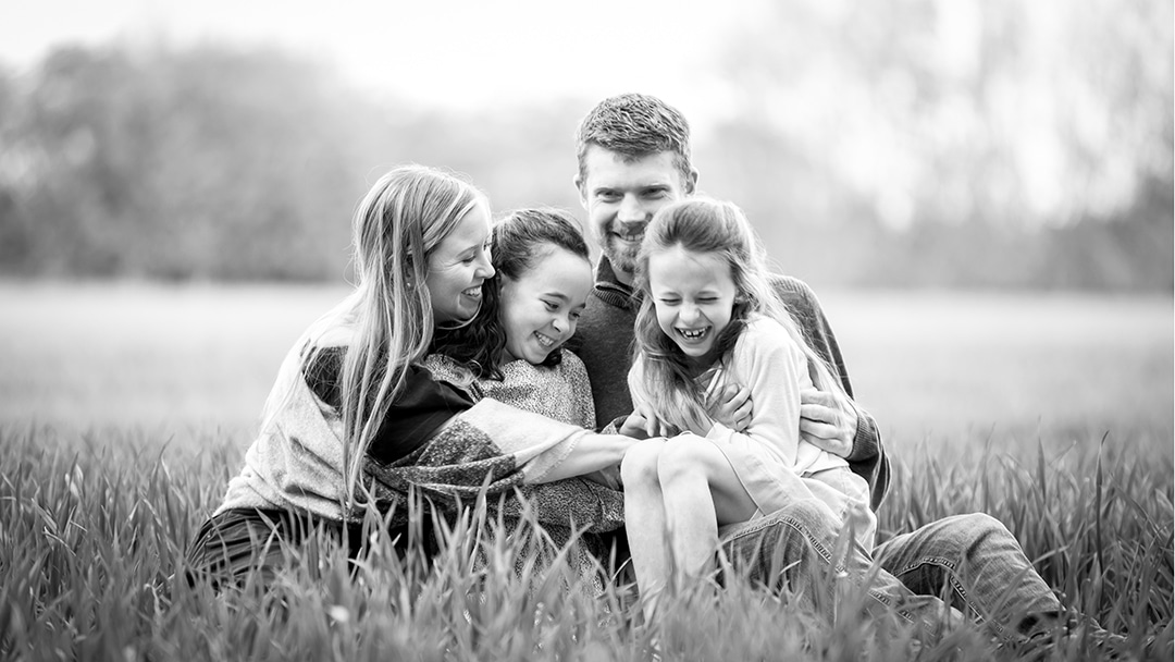 family giggling during a photoshoot in a spring wheat field in cambridge