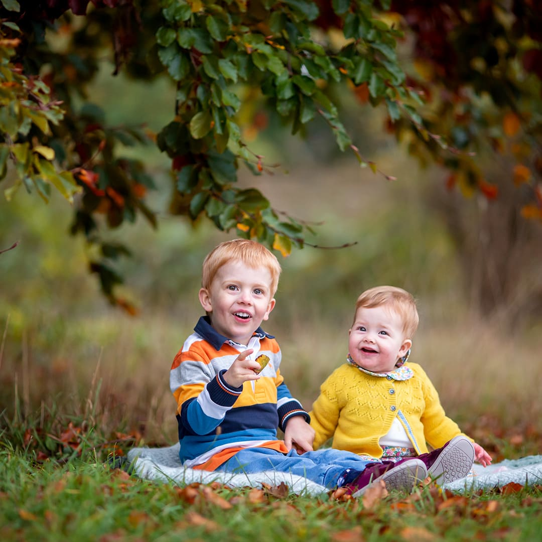 toddler and baby sitting in the autumn leaves under a tree at Wandlebury Country Park in Cambridge