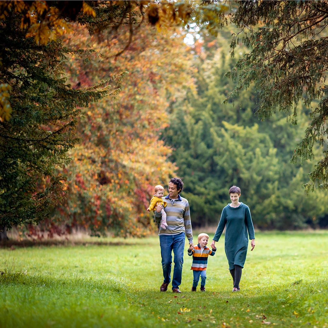family walking through autumn trees during a photoshoot at wandlebury country park in cambridgeshire