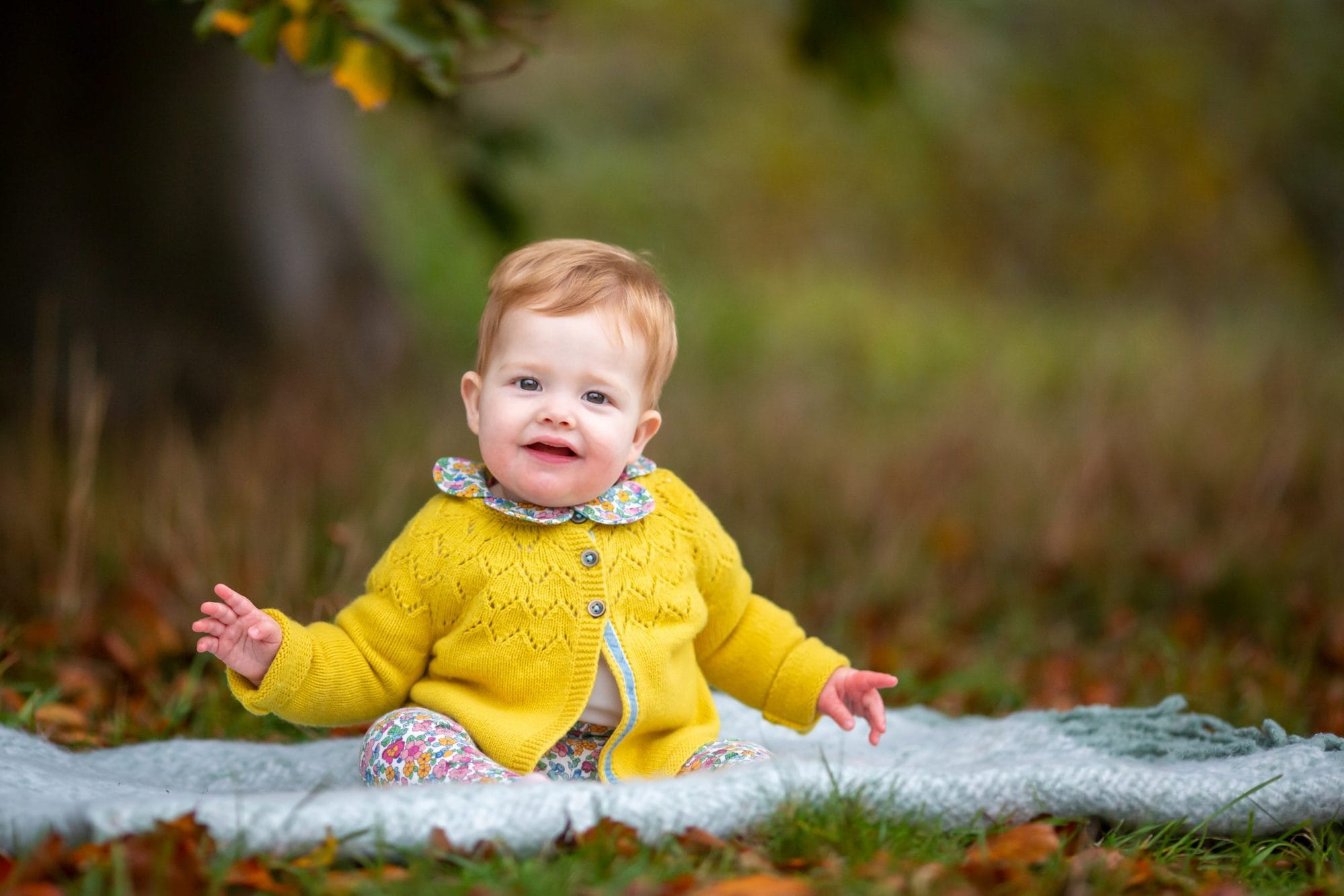 baby girl sitting on a rug in autumn leaves during a family photo shoot in cambridgeshire