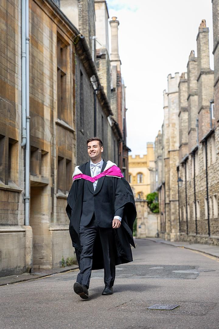 Cambridge student in graduation robes photographed on Trinity Lane