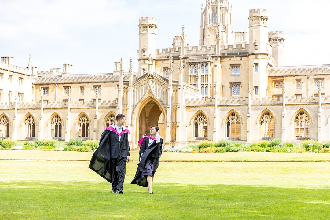 Graduating students on the lawn in front of St Johns college Cambridge during a photoshoot